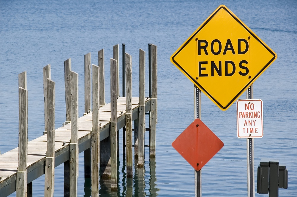 Pier and yellow ROAD ENDS sign by water.jpeg