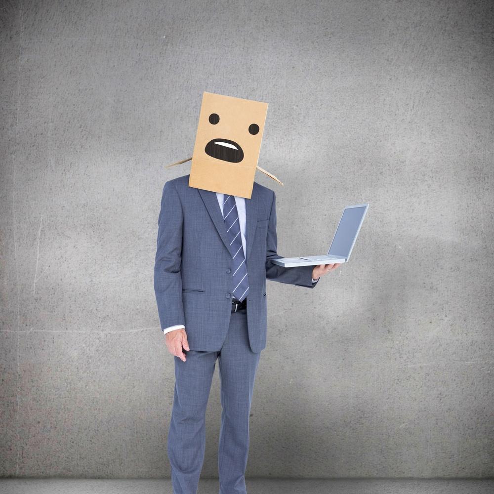 Anonymous businessman against grey room.jpeg