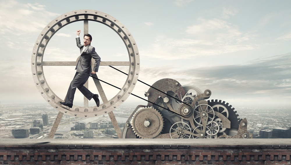 Young businessman in suit running in hamster wheel.jpeg